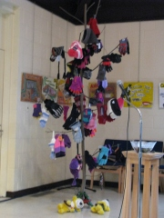 Tree draped with mittens and hats and gifted stuffed bears at the base