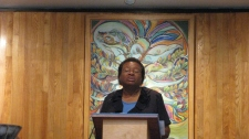 Minister speaking from pulpit in front of mural of tree of life